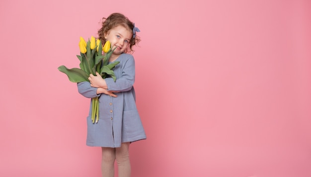 텍스트에 대 한 공간을 가진 분홍색 배경에 노란색 튤립 부케와 블루 드레스에 아름 다운 작은 금발 소녀.