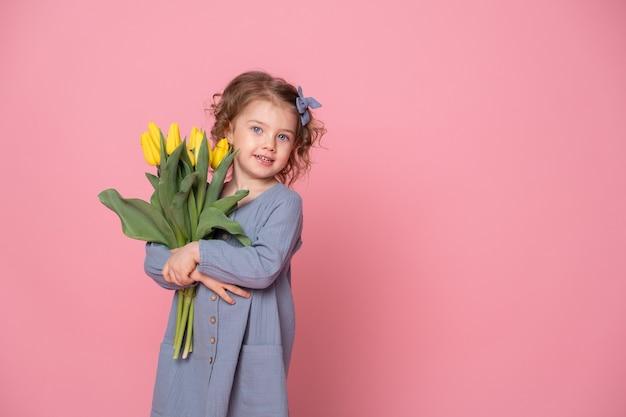 Красивая маленькая блондинка в голубом платье с букетом желтых тюльпанов на розовом фоне