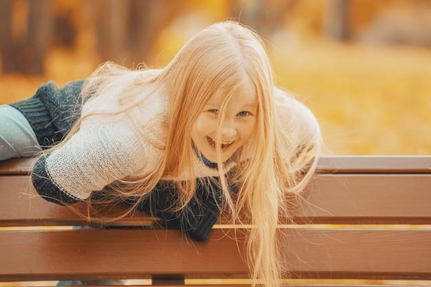가을 공원에서 아름다운 금발 소녀