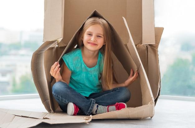 配送ボックスで遊ぶ美しい小さなブロンドの女の子