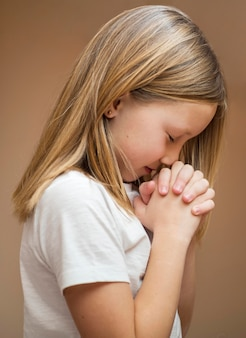 Beautiful little blonde girl praying