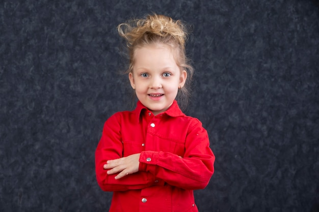 Beautiful little blonde girl in a red dress smiling. five year old child.