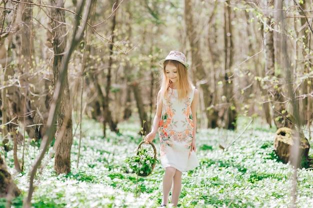 美しい小さなブロンドの女の子は、春の森を歩きます。彼女の頭に帽子とスノードロップバスケットのかわいい女の子の肖像画