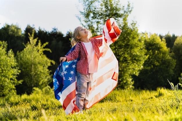 Красивая маленькая блондинка с американским флагом на природе в солнечном свете.