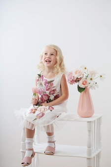 흰색 배경에 꽃과 함께 아름 다운 작은 금발 소녀