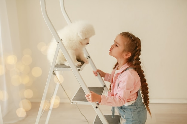 Beautiful little blonde hair girl, has fun smile face, embraces and plays with puppy dog japanese spitz. child and animals portrait. happy amazing couple. autumn time. baby portrait.