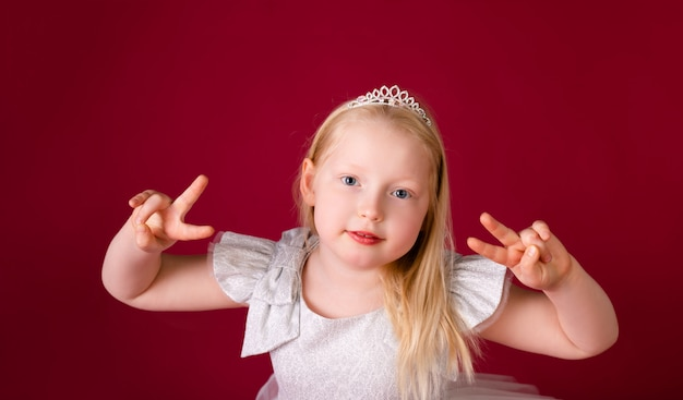 Beautiful little blonde princess dancing in luxury white and silver dress isolated on red background. funny face, different emotions