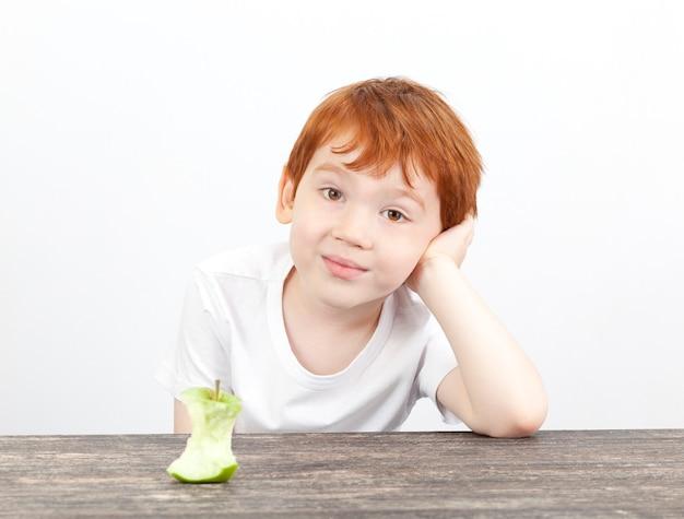 나무 테이블에 누워 사과에서 아름다운 작은 소년과 스텁, 사과는 식사 중에 먹었습니다.
