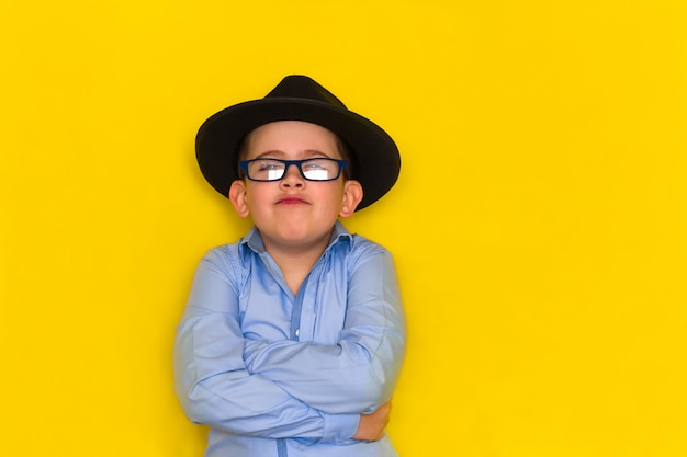 Beautiful little boy in a black hat and blue shirt stands with his arms crossed isolated on yellow