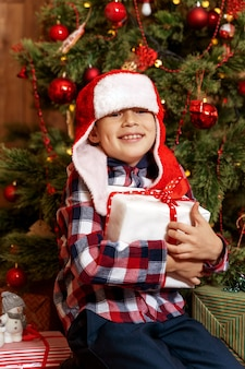 Beautiful little boy next to the christmas tree is happy with a gift