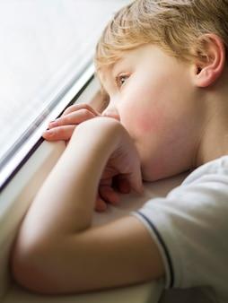Beautiful little boy looking on window