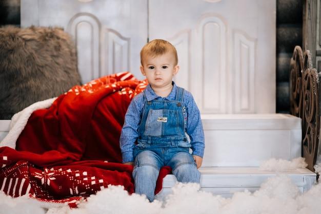 크리스마스 장식 배경에서 아름 다운 작은 소년. 행복 한 크리스마스와 새 해 개념