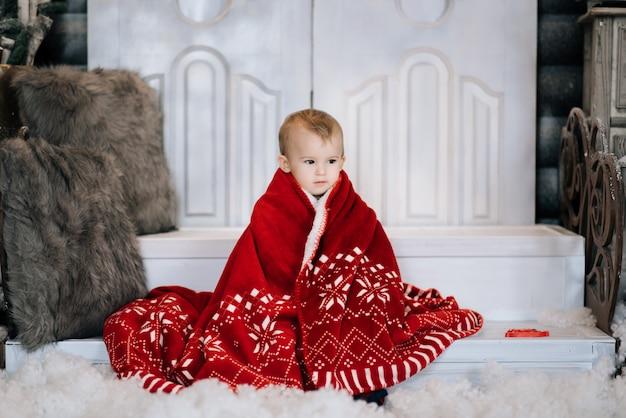 빨간색으로 크리스마스 장식의 배경에서 아름 다운 작은 소년. 행복 한 크리스마스와 새 해 개념