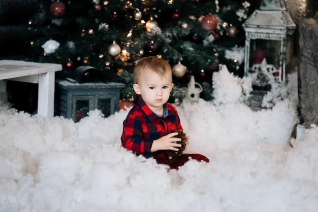 눈에 앉아 크리스마스 장식의 배경에서 아름 다운 작은 소년. 행복 한 크리스마스와 새 해 개념