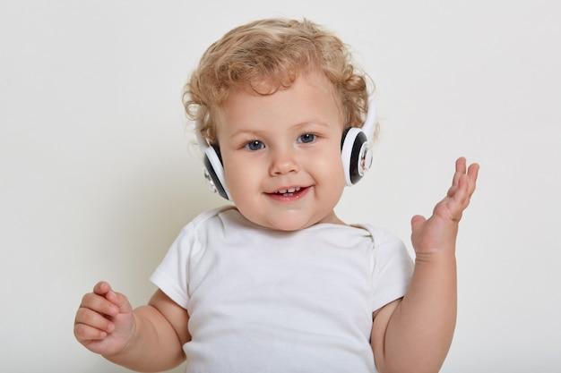 ヘッドフォンで白いスペースに美しい小さな男の子、幸せな笑顔でカメラを直接見て、隠された歯を見せて