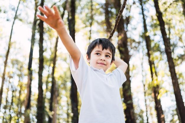 野外で棒で遊ぶ美しい少年
