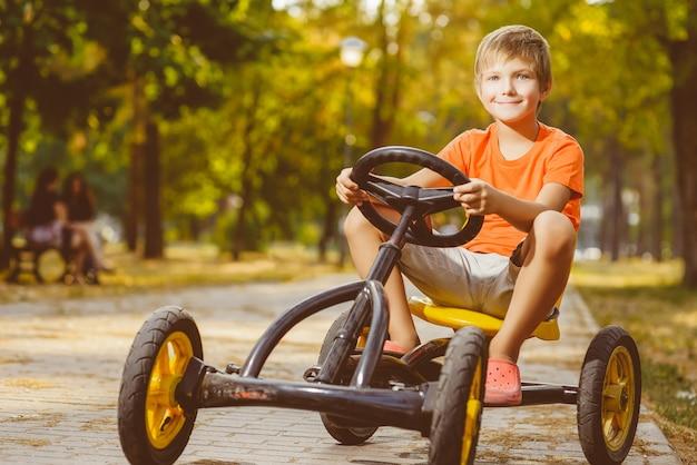 夏の都市公園で美しい小さな男の子乗馬おもちゃの車