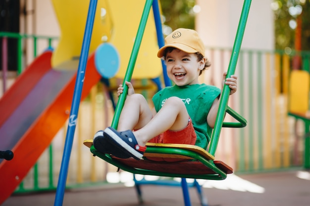 Beautiful little boy spinning on a summer swing with space for text