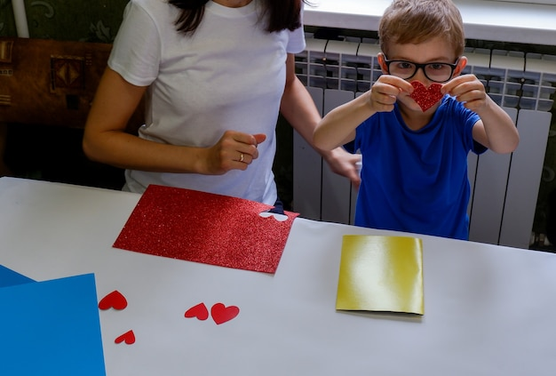 A beautiful little boy with his mother cut a heart out of paper a child makes a greeting card