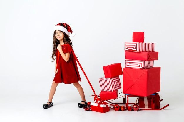 Красивая маленькая брюнетка в костюме санта несет рождественские подарки на санях для текс