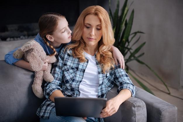 家で母親の注意を待っている美しい小さな思いやりのある子供と母親がインターネットサーフィンやタブレットを使用しながら親を抱き締める