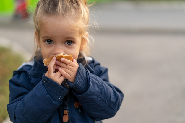 A beautiful little caucasian girl eating bread