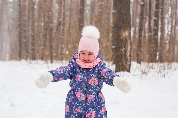 美しい小さな子供の女の子はウィンターパークで楽しんでいます