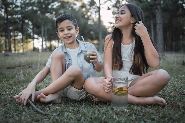 Beautiful little children enjoy a typical argentinean infusion terere
