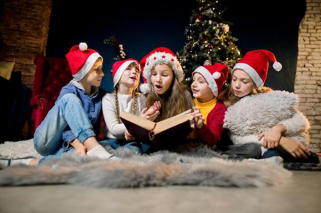 아름다운 어린 아이들이 크리스마스 이야기가 담긴 책을 읽습니다.