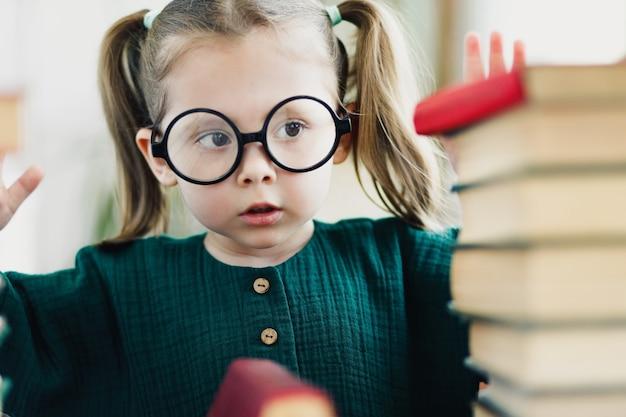 Портрет красивой маленькой умной девушки в очках круглой формы с книгами. селективный мягкий фокус