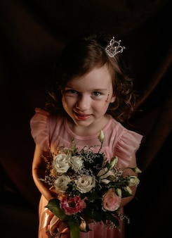 머리에 왕관을 쓴 아름다운 곱슬머리 공주 소녀는 갈색 천 배경에 꽃다발을 들고 있다