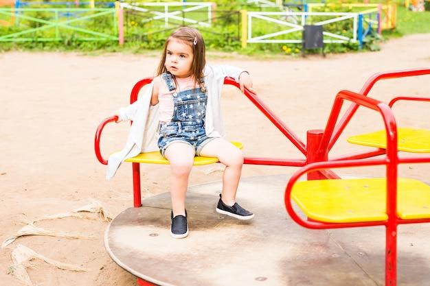 子供の遊び場で美しい小さなかわいい女の子