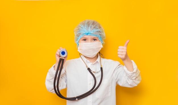 黄色の背景に聴診器を保持している美しい小さな医者