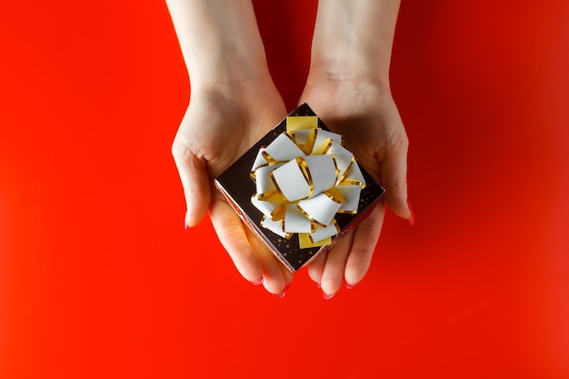 빨간색 표면에 여자의 손에 리본으로 아름 다운 작은 선물. 휴일 선물을드립니다.