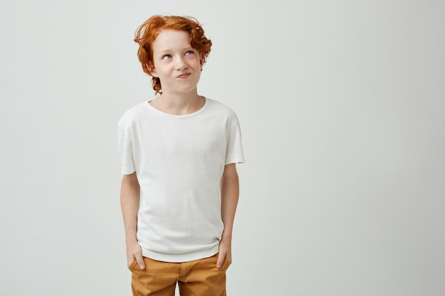 Beautiful little ginger kid in white t shirt and yellow jeans holding hands in pockets, looking aside with funny expression planning something bad.