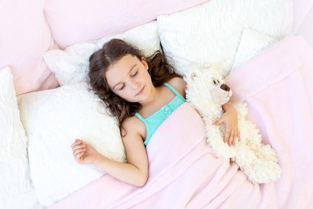 Красивая маленькая девочка 5-6 лет спит в постели с мишкой тедди