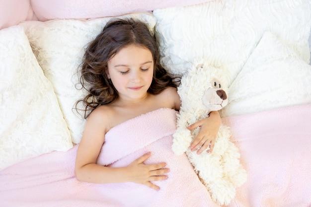 Красивая маленькая девочка 5-6 лет спит в постели с мишкой