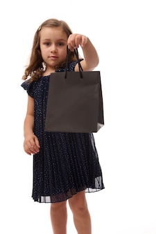 Beautiful little girl, adorable child in evening attire, showing a black shopping packet to the camera, standing isolated over white background with copy space, black friday concept