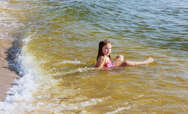 Beautiful little girl bathes in the ocean