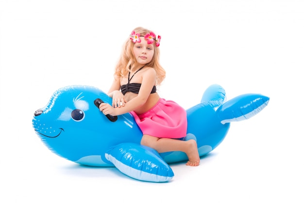 Beautiful little girl in black bikini, pink skirt and pink wreath sit on the inflatable seal