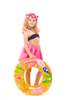 Beautiful little girl in black bikini, pink skirt and pink wreath stand behind rubber ring