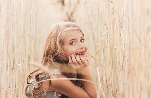 Красивая маленькая девочка блондинка с длинными волосами, идущая через пшеничное поле