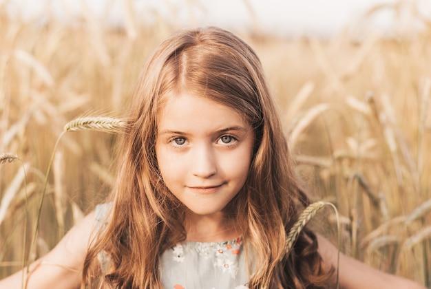 Beautiful little girl blonde with long hair walking through a wheat field