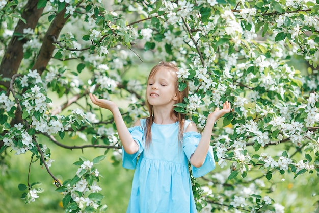 Beautiful little girl in blooming apple tree garden on spring day have a lot of fun