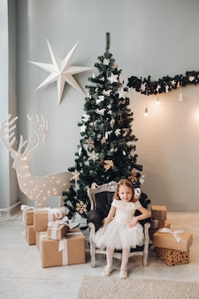 Beautiful little girl by christmas tree. full length stock photo