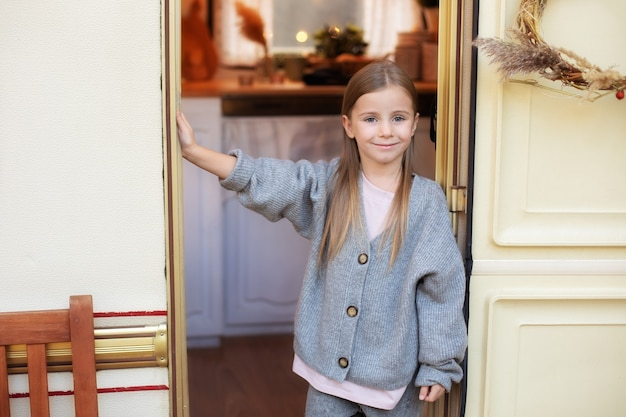 Beautiful little girl in casual clothes standing near trailer door on porch rv house in garden