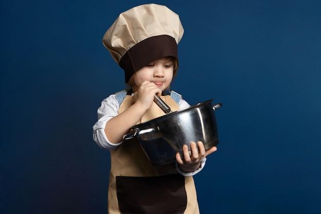 鍋で何かを調理する美しい少女シェフ。エプロンと帽子をかぶった5歳の女性の子供が、ペストリー用のビスケット生地を準備している間、卵白を熱心にホイップします。ベーキングの概念