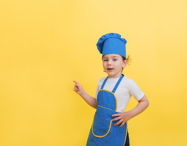 A beautiful little girl in a chef's costume points her finger in the direction. cute girl in an apron and a chef's hat.