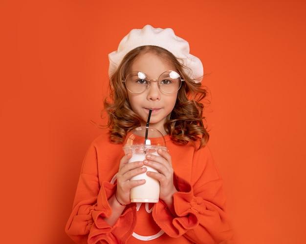 Красивая маленькая девочка 6-7 лет в берете в очках, пить молочный коктейль через соломинку на ярко-оранжевом фоне. фото крупным планом
