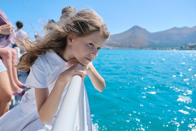 Красивая маленькая девочка, ребенок блондинка с группой туристов, наслаждающихся морским путешествием, солнечным летним днем, живописными пейзажами на горизонте, копией пространства. морская прогулка на небольшом корабле по греческой бухте мирабелло.